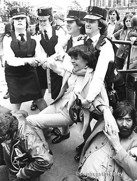 Young woman being grappled by female police officers, Belfast by Stephen S T Bradley, editorial, commercial, PR and advertising photographer, Dublin, Ireland