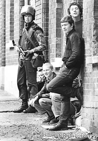 Image - Young British solider on foot patrol beside young men of similar age, New Lodge, Belfast by Stephen S T Bradley, editorial, commercial, PR and advertising photographer, Dublin, Ireland